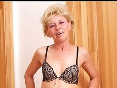 Slender blond cougar Susan Lee masturbates on a bar stool