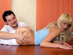 A blonde teenage girl is laying on top of a desk with a guy sitting...